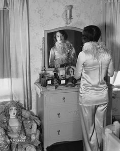 American actress Joan Crawford  standing in front of a mirror spraying her perfume, 1926 - Photo via John Kobal Foundation/Getty Images