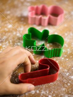 close-up of hand with cookie cutters - Close-up of hand with colorful plastic cookie cutters on butcher board