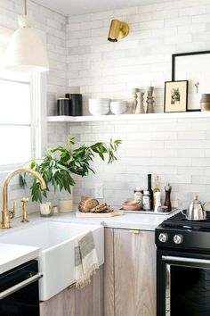 Modern Scandinavian kitchen with black and wooden details. Backsplash goes all the way up the wall.