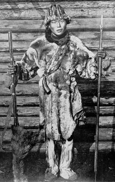 An Orochon in hunting garb. The Orochon are breeders and hunters of reindeer whose nomadic culture and economy are based entirely on that animal. Even their name reflects this. On the left is an old musket, on the right a palma, the wooden shaft surmounted by a blade with which the Orochon formerly hunted bear.   Photo: Lissner - Man, God and Magic