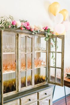 Vintage china cabinet adorned with a floral garland for a garden party