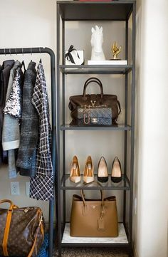 Chic walk in closet features an industrial clothes rack placed next to a metal and glass shelving unit, Ikea Vittsjo Shelving Unit, lined with designer shoes and bags.