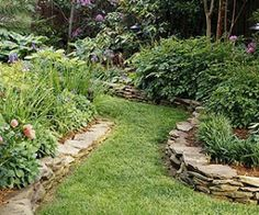 Using stone as garden border. Beautiful. Article suggests curved walkways between beds, as shown.