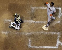 Milwaukee Brewers catcher Martin Maldonado watches as San Francisco Giants' Pablo Sandoval gestures as he steps on home plate on a two-run h...