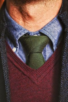 Denim or chambray shirt, cashmere v neck sweater, green wool tie, grey jacket.