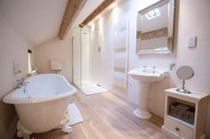 The family bathroom glows with mood lighting and sunlight streaming in from above. Treat yourself to a long lazy soak in the tub.