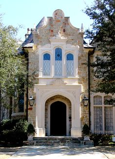 Front entrance with gothic arched surround, stone facade of a English Cotswold Home in University Park, TX