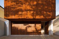 A fachada cega (sem janelas ou qualquer tipo de abertura) ergue-se sobra a caixa retangular, cobrindo-a completamente. - Casa Corten - by Studio MK27