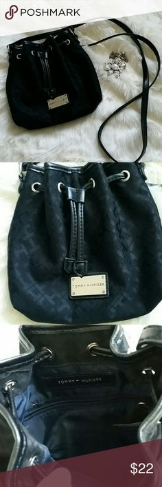 SALE! Small Tommy Hilfiger bucket bag Bucket bags are very trendy!! The small Tommy Hilfiger bag stays right on trend! Preloved but in excellent condition.  Canvas monogram that I want to say is navy blue but in some lights looks black and black leather straps and piping.  Silver hardware.  Strap is 25.5 inches from end to shoulder (so folded in half) Tommy Hilfiger Bags Crossbody Bags