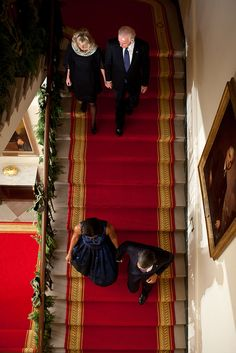 President Barack Obama and First Lady Michelle Obama, along with Vice President Joe Biden and Dr. Jill Biden, descend the Grand Staircase before delivering remarks at a Hanukkah reception in the Grand Foyer of the White House, Dec. 8, 2011. (Official White House Photo by Pete Souza)