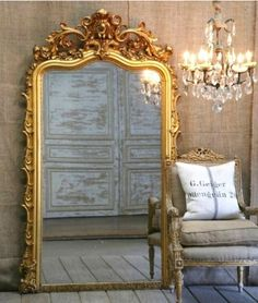 Huge gold french mirror, french chair, and crystal chandelier linen walls!