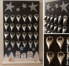 """Calendrier de l'avent 2015 Inspiration """"Village lumineux"""" Pinterest réalisé en carton à partir de l'idée  retravaillée d'Emmanuelle, Rouleaux papier toilette recouverts de papier craft argenté et fermé en bas d'une agrafe, Portes-noms ardoise/pailleté Mesa Bella montés sur une ficelle, Etoiles argentée découpées dans un chemin de table Mesa Bella, support en bois contreplaqué peint à l'acrylique, Fan, champignons et guirlande lumineuse de ma réserve - Dimensions 50x80"""