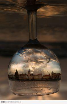 Het glas wordt zo gehouden en gefotografeerd dat je de stad wel helder ziet, waardoor dit een interessant plaatje wordt.