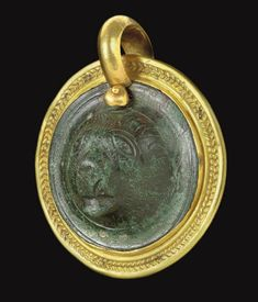 A ROMAN BRONZE ROUNDEL   CIRCA 2ND-3RD CENTURY A.D.   In the form of the head of a bear, the eyes and snout incised, the fur rendered by stippling; set as a pendant in a modern gold moun
