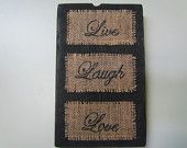 """Old Barn Wood Wall Hanging That Says """"Live Laugh Love"""" In Black Cursive Font On Burlap"""