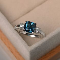 This ring features a 7*7mm cushion cut London blue topaz and sterling silver finished with rhodium. Customization is available. It is made by hand, and it will take about 7 days to finish the ring after your payment is completed. Main stone: London blue topaz weight: Approx 2.2 ct Metal
