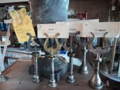 Musical instrument repurposing, continued:  Old trumpet and other horn mouthpieces are paired with vintage lyres/music holders for use as placecard holders.  (Via Daily Danny; photo taken several months ago at Vintageweave in Los Angeles.)