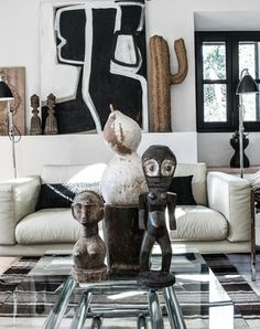 A modern living room with strong tribal vibe from the decor. Handcrafted figurines & other artworks. Contemporary vibe from sofa, striped area rug, coffee table, lamps;