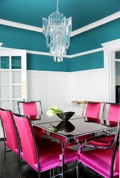White molding and a bold wall color, crystal chandelier and a metal dining table with hot pink chairs. Wall color is Benjamin Moore North Sea Green 2053-30 Flat.
