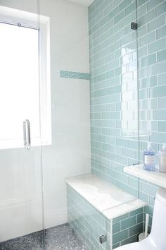 Contemporary bathroom features a seamless glass walk in shower lined with blue glass subway shower tiles and a shower bench above the gray mosaic shower floor.