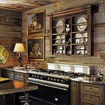 The walls and ceiling in the kitchen of a log cabin–style home in the foothills of Tennessee's Great Smoky Mountains are clad with salvaged wood. Interior designer Suzanne Kasler decorated the space with a pair of 18th-century French still lifes and a 19th-century English-oak rack.