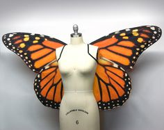 Realistic monarch butterfly Halloween costume wings. These wings are made to order. The current processing time is 1-2 weeks.   These wings measure about 50 inches (wingspan). They are constructed the same as the smaller version except with thicker wire.  They attach to the body with two pieces of elastic (one for each shoulder like a backpack). This listing is only for wings, the wings look good with a black knit dress or leotard.  If the wings get wrinkly, they can be ironed (avoid ironing…
