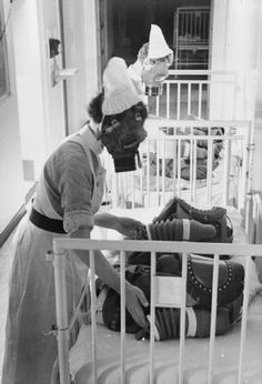 Two nurses each pump the bellows of a baby gas respirator in order to supply the child wearing the mask with air, during a gas drill at a London hospital, 1940.