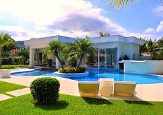 Ao centro, a piscina com prainha, ilha e queda d'água é uma das opções para se refrescar nos escaldantes dias de sol. Espreguiçadeiras relaxantes foram dispostas ao redor da piscina e garantem a manutenção do bronzeado.