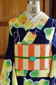 濃紺色地に、綺麗なグリーンから、黄色、オレンジへとぼかされたビタミンカラーも愛らしく、レトロポップキュートな薔薇のようなお花模様が染め出された注染の浴衣です。