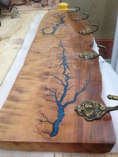 Live edge Pear wood clothes hanger with glow in the dark Lichtenberg figure blue resin inlay and ancient bronze hooks.