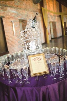 Champagne glasses awaiting a toast arranged around a bubbly ice sculpture.