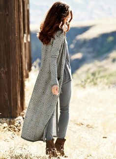 The maxi-length cardigan is knit in a pre-Columbian bas-relief of salt and white pepper diamonds. In soft, lightweight baby alpaca, the straight-falling silhouette has a crewneck, welt pockets and pinstriped trim.