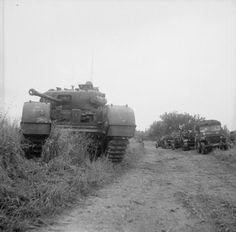 A Churchill tank of 7th Royal Tank Regiment, 31st Tank Brigade, with jeeps and loyd carriers of the 15th scottish division with there 6 pounder fieldguns during Operation 'Epsom', 26 June 1944. ( note the female art work on the churchill's fender ).