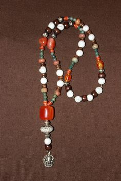 Necklace with white Turquoise beads, brown wood beads, Tibetan silver spacers, orange plastik beads, green glass beads, Picasso Jasper rondelles, brown coconut wood rondelles, Amber beads, a silver capped white rhesin bead & a Ganesha amulet pendant. 40€.