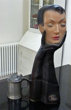 This is an unusual vintage plaster mannequin of a very stylish young lady holding her head in her hands, and with a rather pensive expression on her face. It was made for the French fashion house Christian Dior as an advertising item to help promote sales of their fashion products. It is hollow and is manufactured from some kind of plaster, with a matte painted finish. Id estimate that it probably dates to around the 1960s/70s. It would be ideal as part of a collection of advertising it...