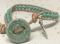 This bracelet features little jade green Swarovski pearls which have been attached to tan leather cord. A beautiful handmade ceramic button has been used as a fastener and a small silver coloured feather charm adds the finishing touch. Leather Cord, Tan Leather, Wrap Bracelets, Organza Gift Bags, Swarovski Pearls, Jade Green, Silver Color, Washer Necklace, Ceramics