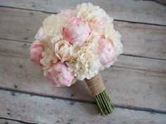 A beautiful shabby chic bouquet with a vintage feel. Eighteen ivory and blush pink roses and peony buds are accented with ivory hydrangeas and tied with burlap wrap. This wedding bouquet measures 10 i