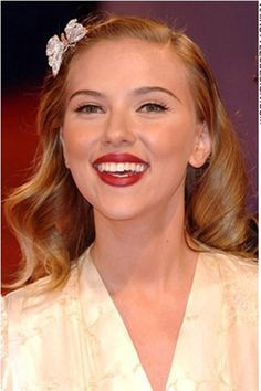 This hairstyle is a retro 50's look. Very glamorous and chic, Scarlett looks incredibly beautiful. Her long hair is styled with a slight side part with slight curls all around. In the front the hair is combed back leaving her face clear from any straying hair.
