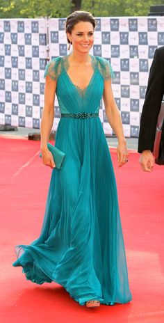 The Duchess wore Jenny Packham Spring 2012. She look beyond in a stunning jade green chiffon gown with lace cap details in the back and shoulders/sleeves. Her back was lined along the spine with Swarovski crystals. She accessorize with tear drop earrings and added a jeweled belt to accentuate her waistline.  Jimmy Choo Vamp Sandals and a matching clutch.