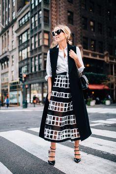 Black and white: black midi textures skirt with white shirt and black sleeveless jacket.