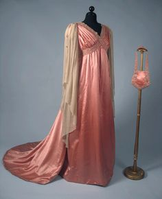 ROSE PINK EVENING GOWN, 1910 Silk satin Aesthetic style, high waist, beaded & pearl trimmed bands that criss-cross around bustline, trained skirt, long Renaissance style cream chiffon sleeves w/ pearl & beaded edge, matching small shield shaped evening bag.