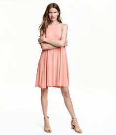 Powder pink. Short jersey dress with narrow shoulder straps. Opening at back with button at back of neck. Narrow cut at top and flared to hem. Lined at top.