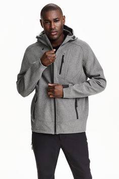 Softshell jacket: Softshell jacket in windproof functional fabric with a hood with an elastic drawstring and small peak, a zip at the front and zipped side pockets. Chest pocket with a zip and earphone outlet on the inside and elastication at the cuffs and hem. Thermal fleece inside. Regular fit. Size of chest pocket approx. 12x17 cm.