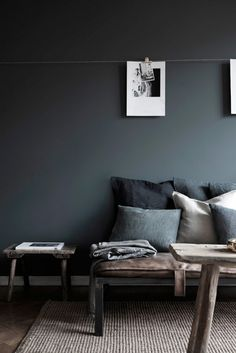 Gray sofa with pillows against charcoal wall.