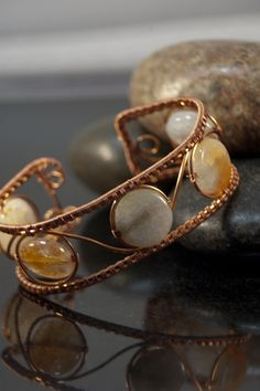 These lovely light blue and sun kissed orange 16 mm SunAgate disks are fashioned into a 24 mm (1 inch) wide bracelet made from sealed wire woven copper wire.