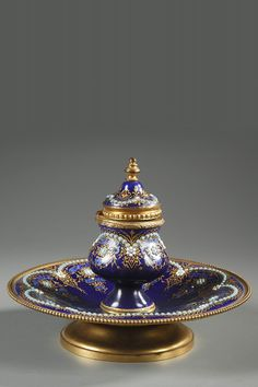 A small inkstand in blue Bresse enamel with gilt bronze mounts composed by an inkwell with its hinged lid and a cup finely decorated with arabesques in gold thread, rinceau...