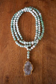 Long beaded necklace with assorted green beads and a large white druzy stone