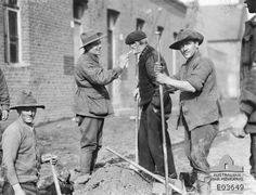 An old French villager, liberated by the Allied advance, enjoying the luxury of a cigarette given him by a member of the 1st Australian Tunnelling Company, which on this date was repairing a road through the village. Left to right: 3485 Sapper (Spr) J. J. McKinnon; 337 Second Corporal R. J. Tracy; French villager; 3640 Spr A. A. Moore. Western Front: Western Front (France), Nord Region (France), Busigny. 26 October 1918.