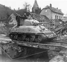 M4A1 Sherman Tank of the 741st Tank Battalion, attached to 2nd Infantry Division., U.S. First Army, crosses an improvised bridge in Germany, 9 March 1945. Note the Rhino device (hedgerow cutter) on the front.