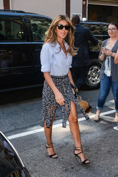 Nina Garcia wears a blue button-down shirt, gray car-wash pleat skirt, and lace-up sandals